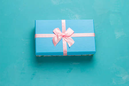 top view blue  present box with festive pink bow on a blue background