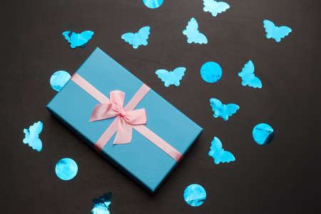 blue gift box with festive pink bow on a black background background with blue holographic confetti top view flat lay Imagens