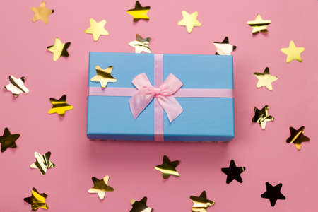 top view beautiful blue gift box with pink satin ribbon with bow on a pink background with golden stars sequins Imagens