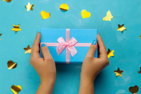 top view female hands holding blue gift box with festive pink bow on a blue background with golden confetti