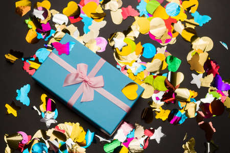 top view beautiful blue gift box with pink satin ribbon with bow on a black background with  stars and butterfly sequins Imagens