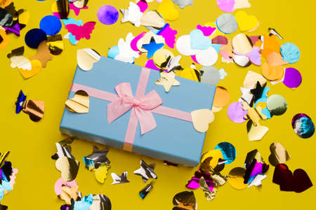 top view beautiful blue gift box with pink satin ribbon with bow on a yellow background with  stars and butterfly sequins