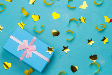 blue  present box with pastel pink bow on a blue background with golden confetti