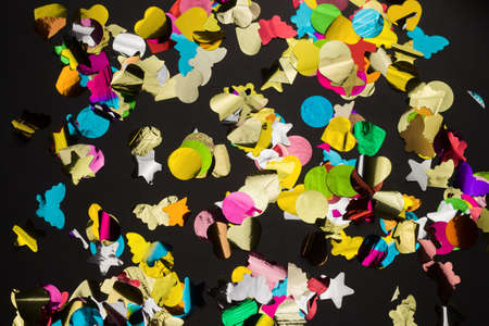 top view multicolored confetti mess on a black background,abstract holiday background