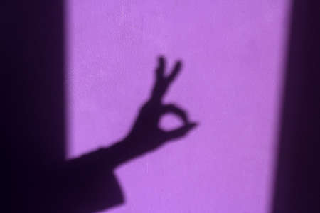 purple shabby wall with palm shadow with OK sign Stock fotó