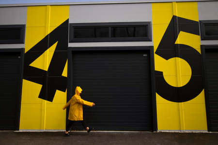 woman in yellow raincoat walking from number four to number five Imagens