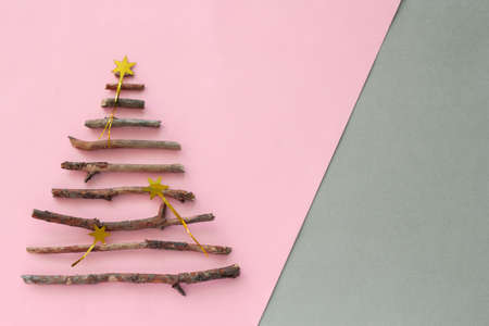 top view christmas tree silhouette  made from wooden twigs and  on a pastel pink and gray background with copy space