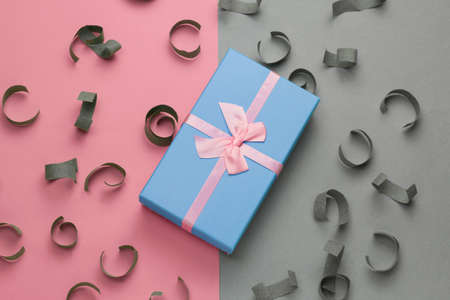 blue gift box with festive pink bow top view on a gray and pastel pink background with paper confetti