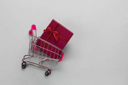 shopping cart with red present box on a gray background copy space