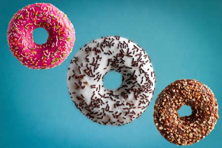 sweet  glazed donuts flying over blue background, junk food concept Stockfoto