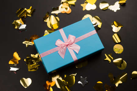 top view blue present box with pink festive bow with golden confetti on a black background Imagens