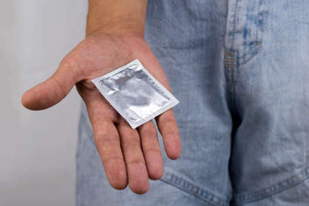 close up of male hands holding a condom pack  , safe sex concept