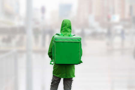 unrecognizable  young man courier in green jacket with green backpack on a background of blurred city