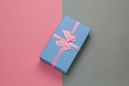 top view blue gift box with festive pink bow on a gray background with pastel pink frame with free space for text