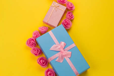gift boxes and pink roses flat lay on a vibrant yellow background with free space for text Stock Photo