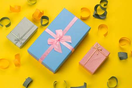 top view three bright present boxes on a vibrant yellow background