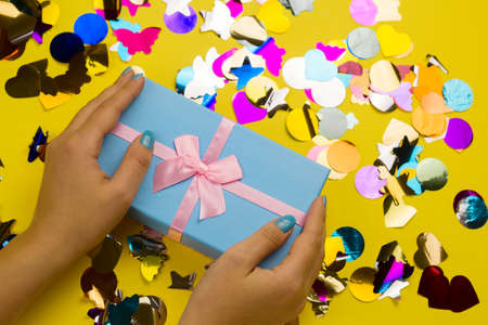 top view female hands holding blue gift box with festive pink bow on a yellow background with holographic multicolored confetti 版權商用圖片