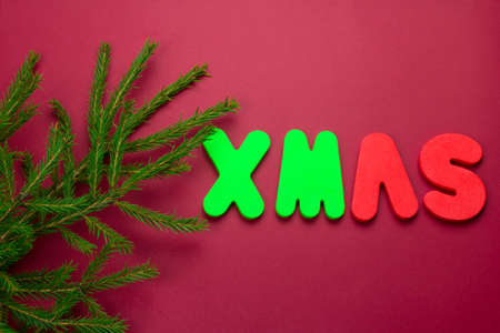 top view evergreen tree branches on a red background with word xmas