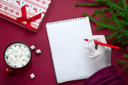 top view flat lay sheet of blank paper with space for text and Santa Claus hand in white glove , fir branches, gift box and cocoa cup on a red background Stok Fotoğraf