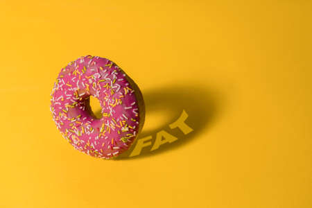 pink donut on a yellow background with a shadow with  word fat , unhealthy nutrition and lifestyle concept