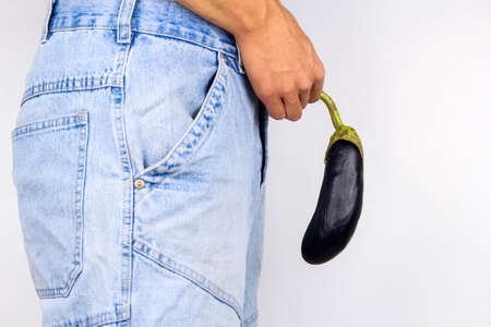 young man holding eggplant near  his crotch