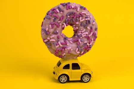positive card with retro yellow car delivering sweet pink donut Archivio Fotografico - 133311459