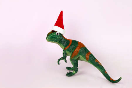 funny green dinosaur toy in little santa claus hat