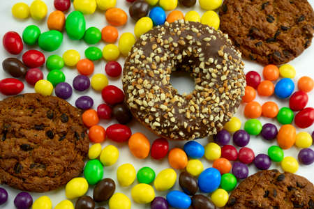 sweet colourful candies, cookies and donuts top view, unhealthy lifestyle and diet concept