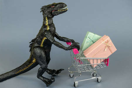 plastic dinosaur toy with shopping cart full of present boxes Standard-Bild