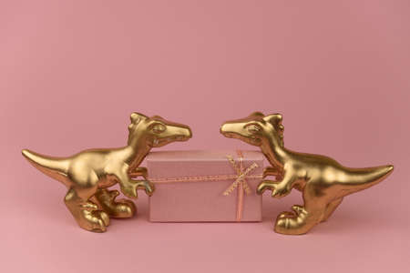 golden dinosaurs with gift box  a pastel pink background, trendy modern christmas card with copy space