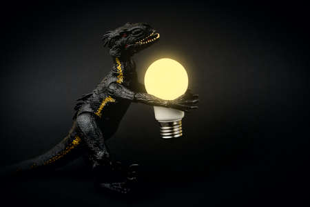 black dinosaur holding a lamp on a black background Archivio Fotografico