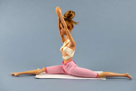plastic doll in yoga pose on a gray background , healthy lifestyle concept
