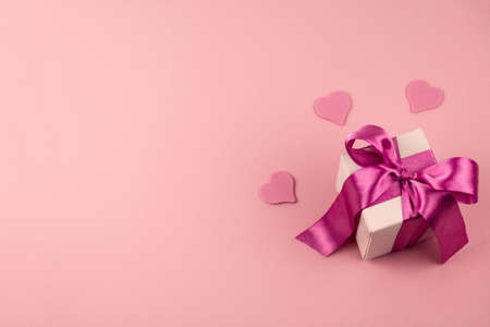 top view gift box with festive satin ribbon bow and three hearts on a soft pink background with copy space Banque d'images