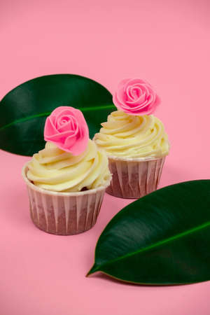 sweet cupcakes decorated with roses and tropical leaves on a pastel pink background selective focus Foto de archivo