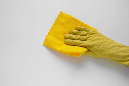 hand in yellow rubber glove wipes white wall with yellow cotton cloth, cleaning service concept