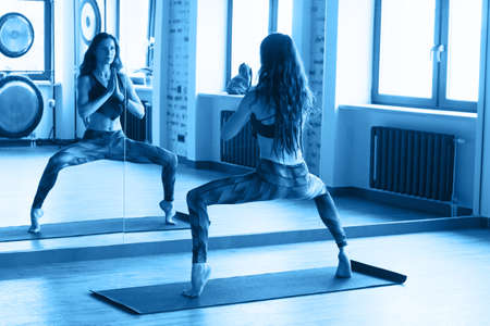 beautiful caucasian woman with long hair and slender body doing stretching exercise near mirror in dance class