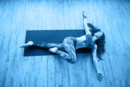 beautiful caucasian woman with long hair and slender body doing yoga on a mat top view 写真素材