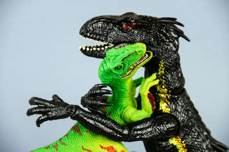two plastic dinosaurs hugging each other