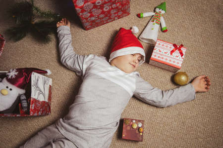 cute little boy in gray pajamas and Santa hat sleeps on the floor under a Christmas tree among festive gift boxes