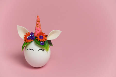 cute spring Easter card with an unicorn egg with a rim of spring flowers and horn  with copy space on a pastel pink background Stockfoto