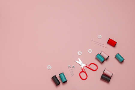 top view flat lay red ,pink and and blue sewing or embroidery supplies on a soft pink background with space for text