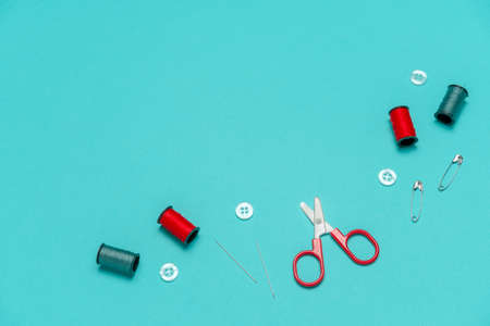 top view flat lay red and blue sewing or embroidery supplies on a blue background with space for text