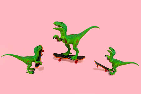 collage of three cute green dinosaurs skate isolated on a pink background Stock Photo