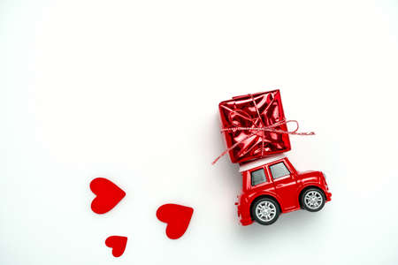 Valentines card with little red toy car carrying red gift box and red hearts on a white background