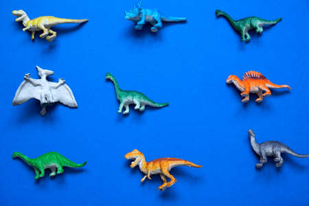 top view creative layout with little plastic dinosaurs on a blue background 免版税图像