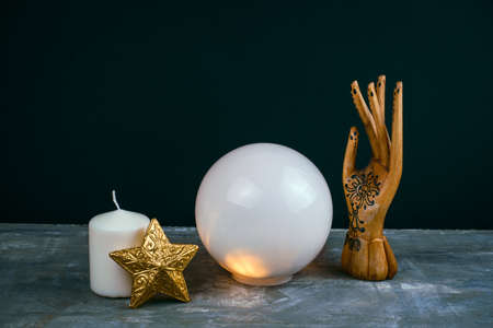 creative esoteric still life with a ball of predictions , wooden female hand and candles on a concrete table against  black background