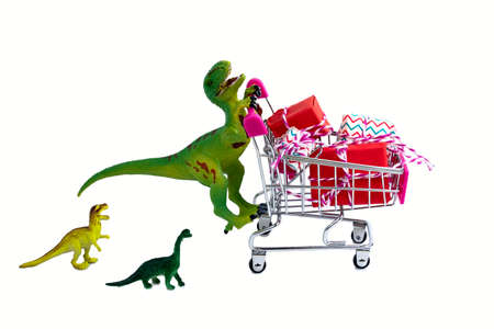 funny green dinosaur toy with shopping cart full of present boxes and little dinosaurs kids isolated on white background