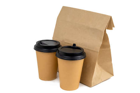two disposable paper cups and a paper bag with food isolated on a white background