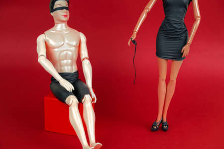 blindfolded man and a woman in a black leather dress holding a whip on a red background, a creative still life with plastic dolls sex concept