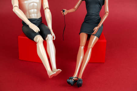 man and a woman in a black leather dress holding a whip on a red background, a creative still life with plastic dolls sex concept 스톡 콘텐츠